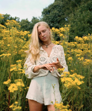Indie folk musician Billie Marten from the United Kingdom standing in a field of flowers; under the radar artists you should know about