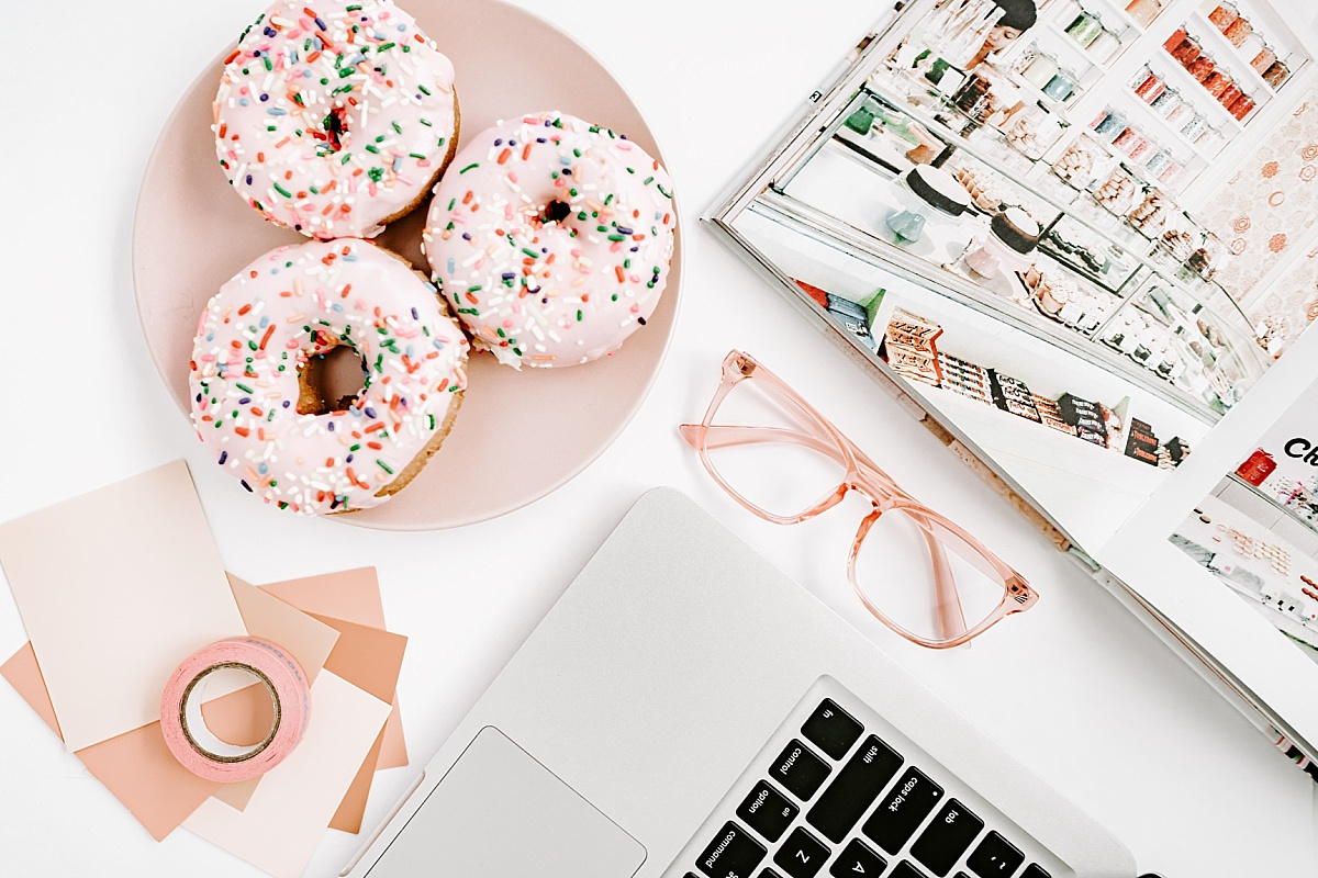 CRM Dubsado marketing image of a cute flat lay with pink sprinkled donuts, a macbook, a magazine and pink glasses