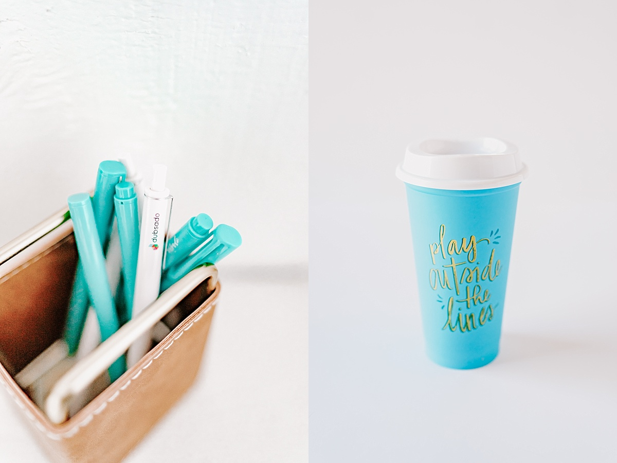 Dubsado branded blue and white pens in a pen holder beside a blue thermos with the words 'play outside the lines'