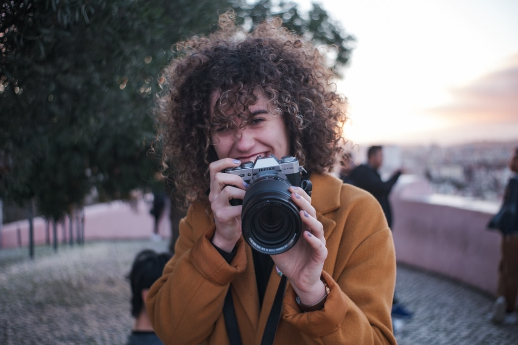 Female photographer holding a camera and smiling at the camera.