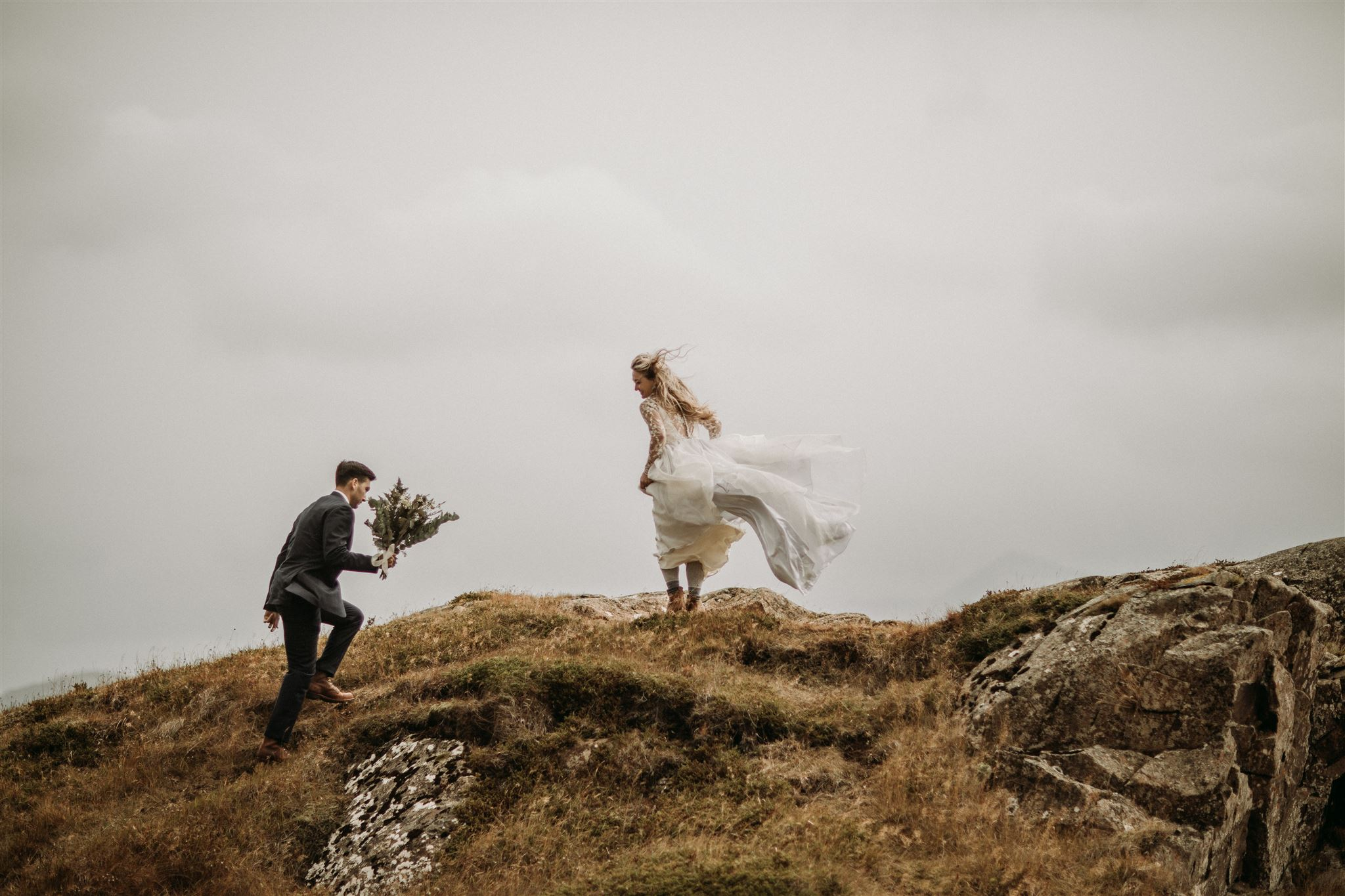 Bride and groom walking on rolling hills in Iceland during their iceland elopement with Stephanie Zakas Photography