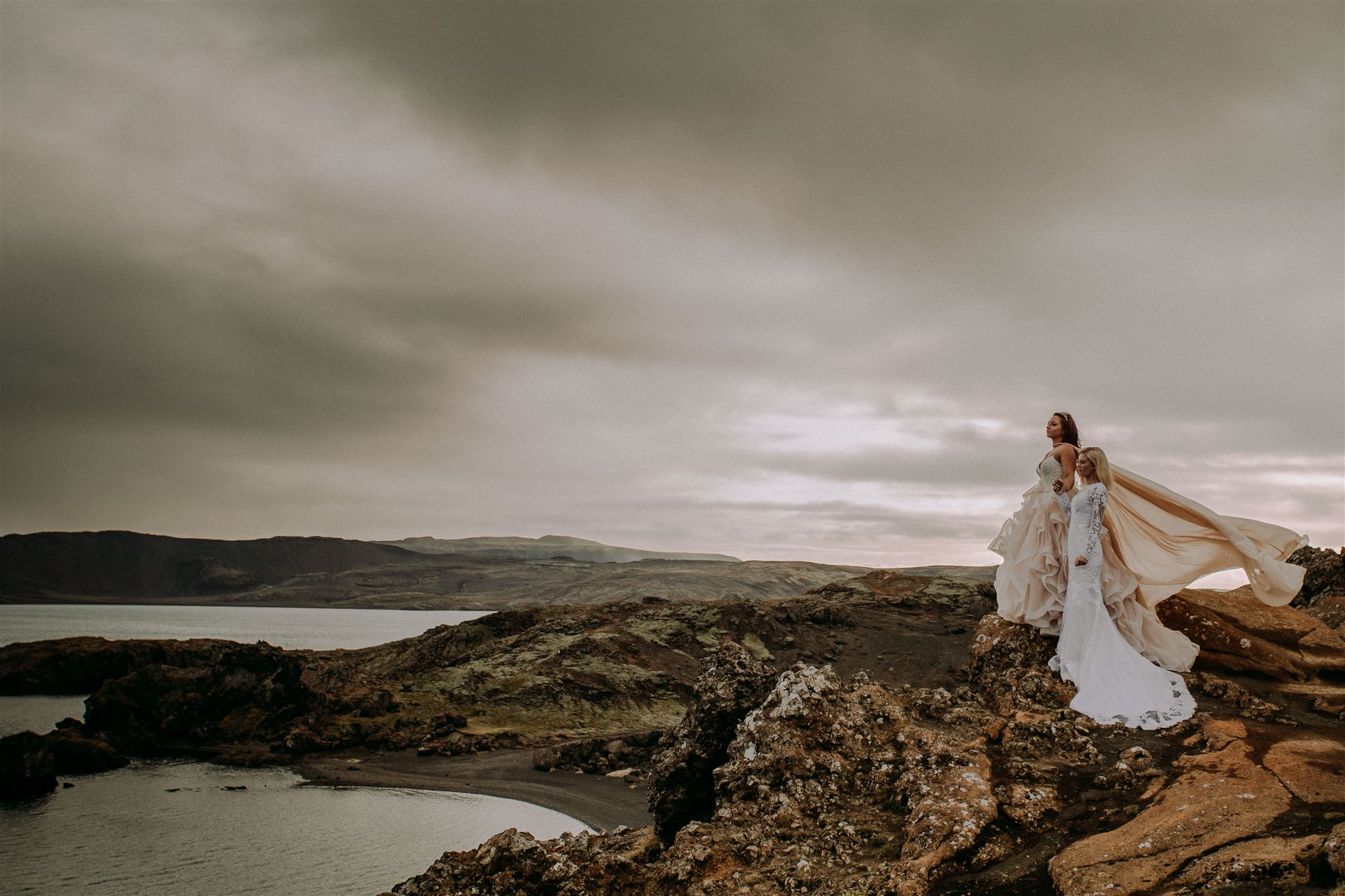 Two brides wearing different wedding dresses shot by Steph Zakas Photography during photoshoot in Iceland.