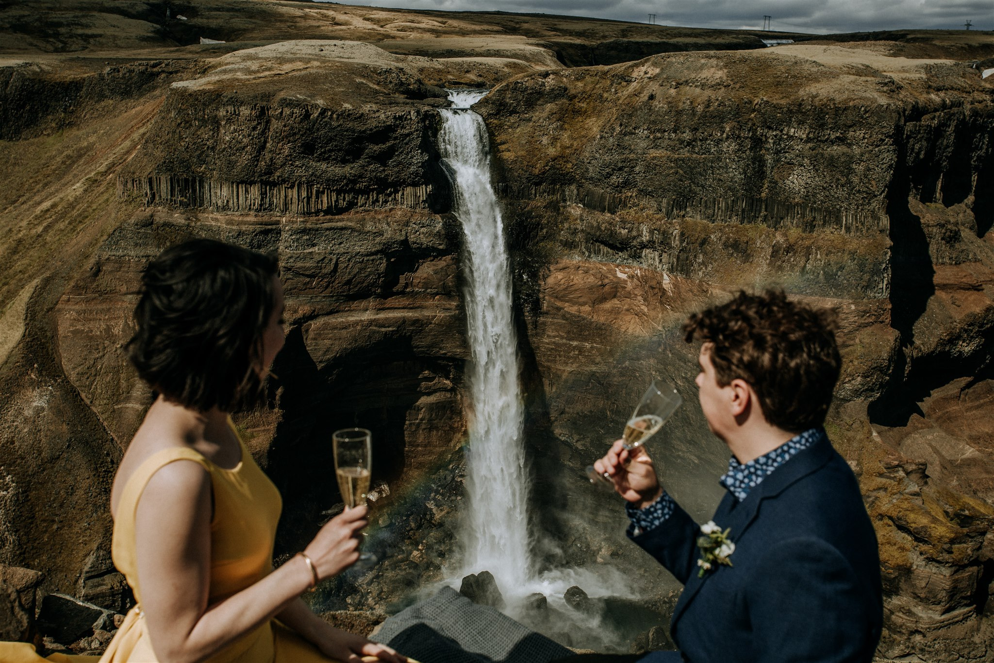 Bride and groom drinking champagne by a waterfall after their elopement in Iceland by Stephanie Zakas photographer