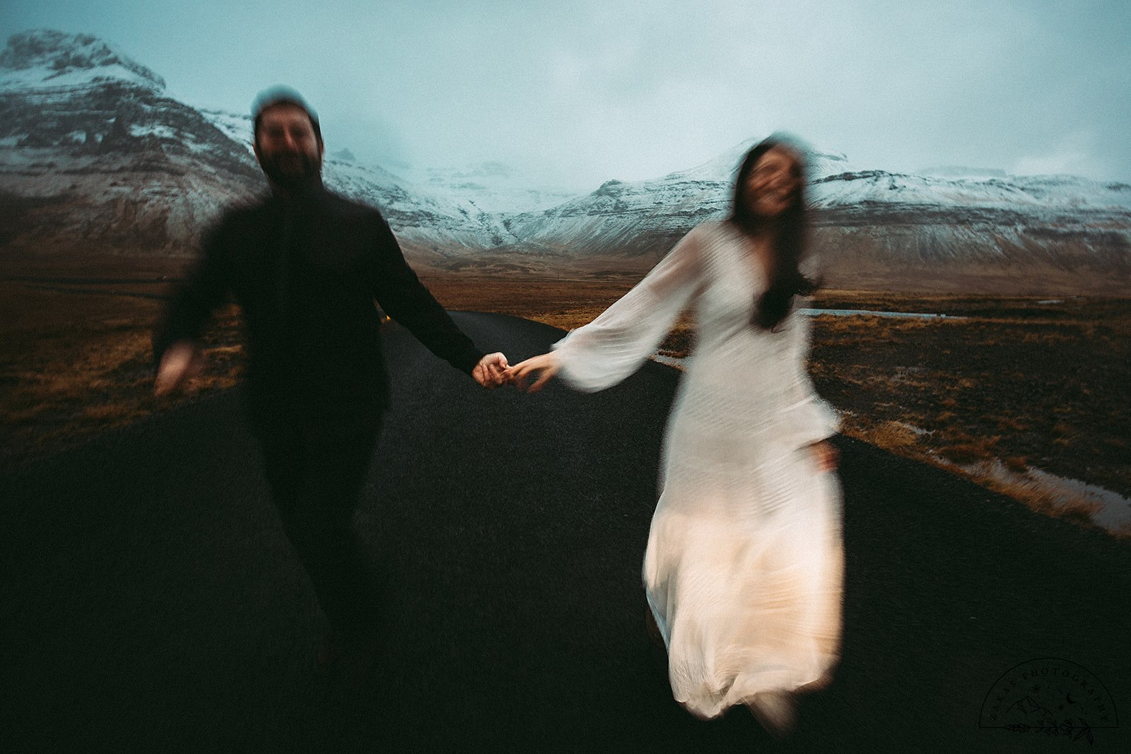 Husband and wife running down highway celebrating their honeymoon in Iceland.