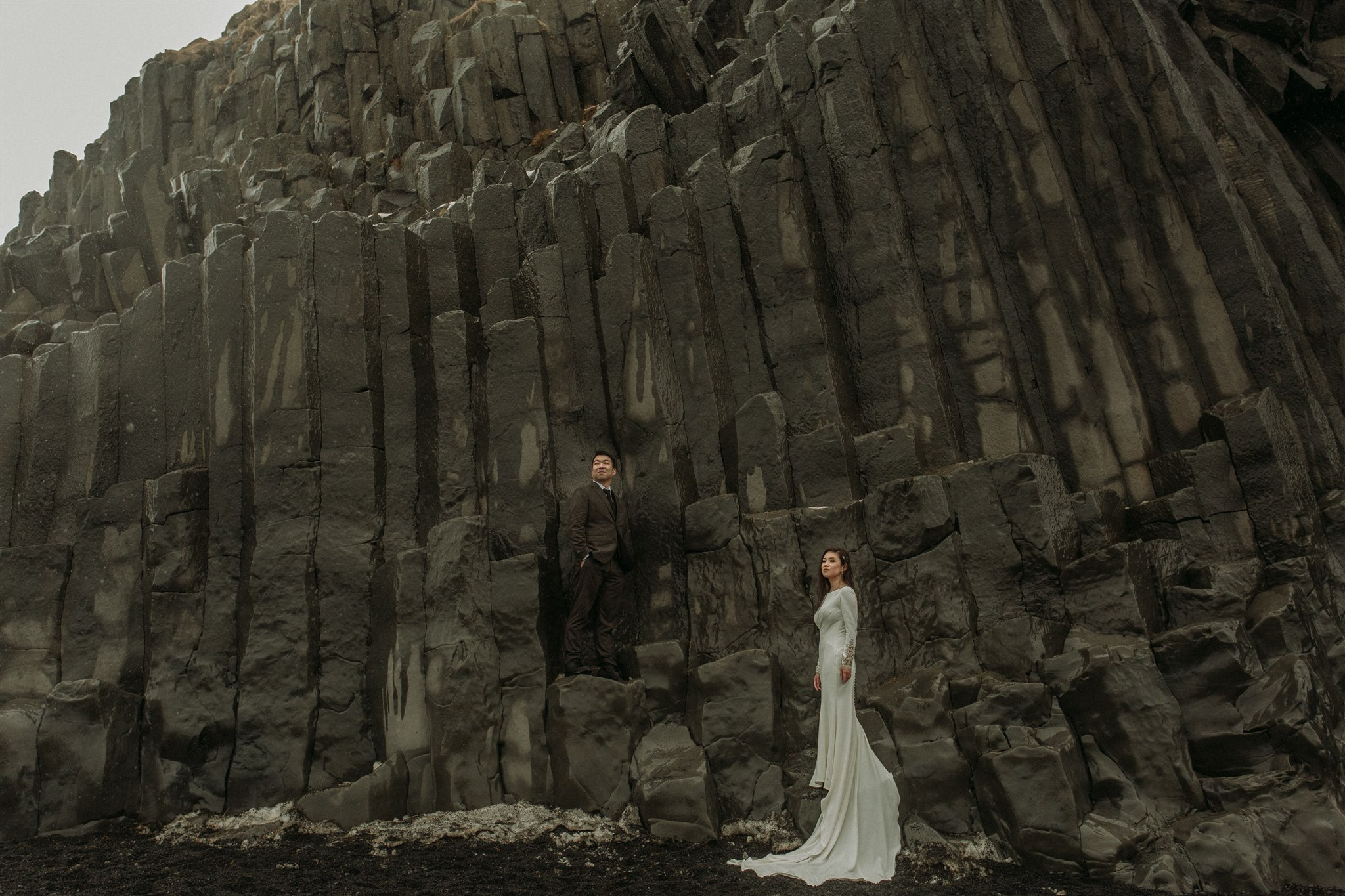 Bride and groom posing for photos taken by Steph Zakas Photography, in front of rocks during Iceland elopement.