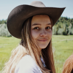 young white woman with long hair and a cowboy who is a Graphic designer at Pepper smiles while talking about publish by narrative