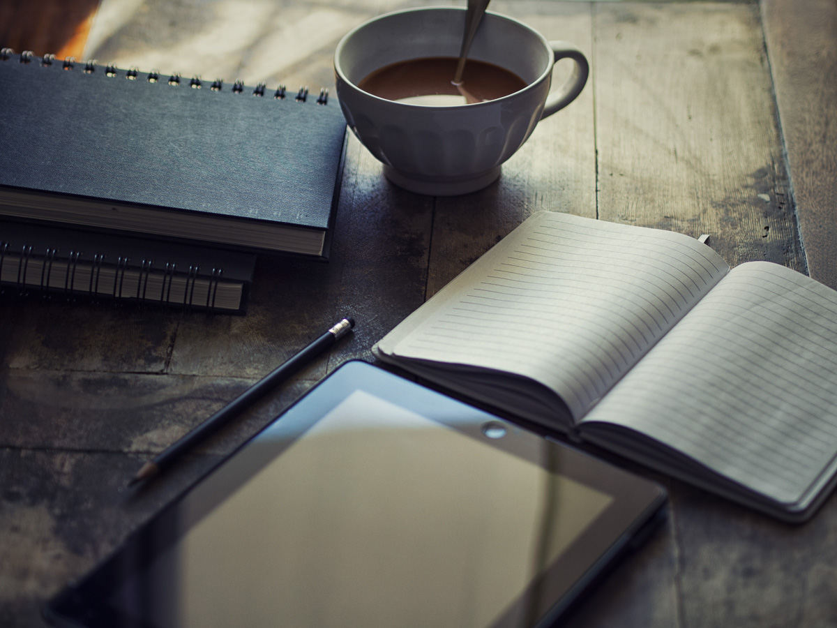 coffee cup, notebook, iPad and pencil laid out on a table to make client notes for an album in StompSoftware