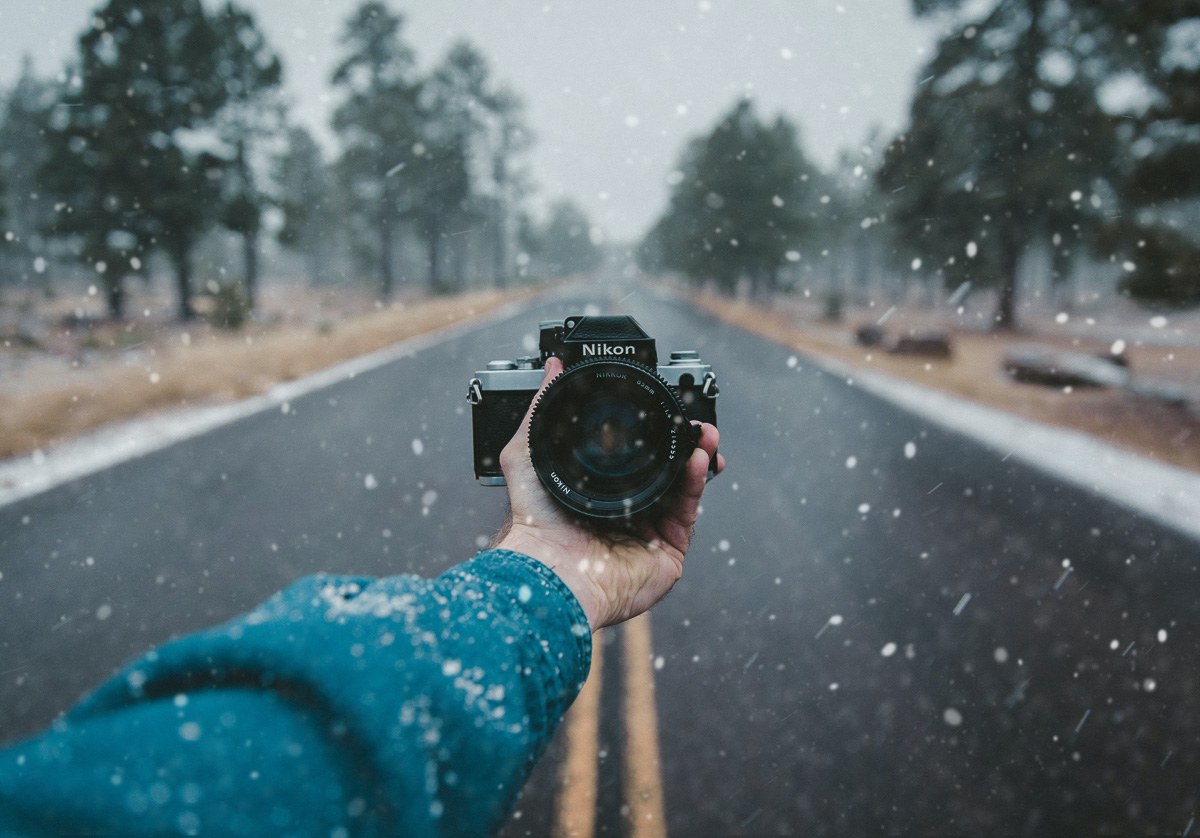 hand outstretched holding a digital SLR camera to take a selfie in a light snowfall as part of an album by StompSoftware
