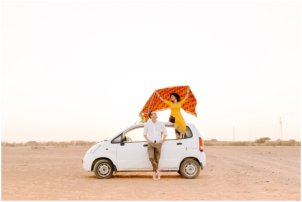Sirjana and Ben from Tinted Photography, recently interviewed on the PepperCast, standing with their car in the dessert.
