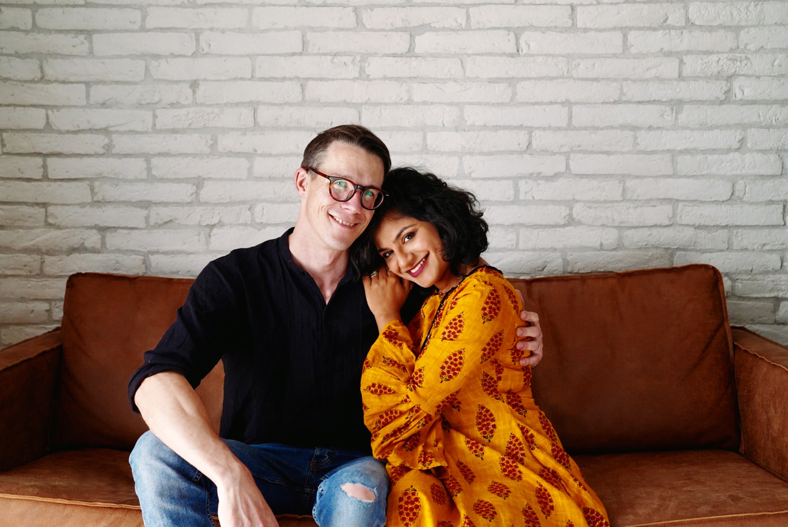 Ben and Sirjana from Tinted Photography sitting together on a brown couch in front of a white brick wall.