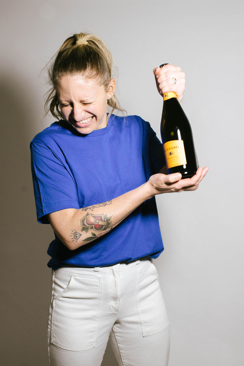 jess robson, communication coach, wearing white jeans and blue T holds a champagne bottle and makes a funny face while preparing to open it.