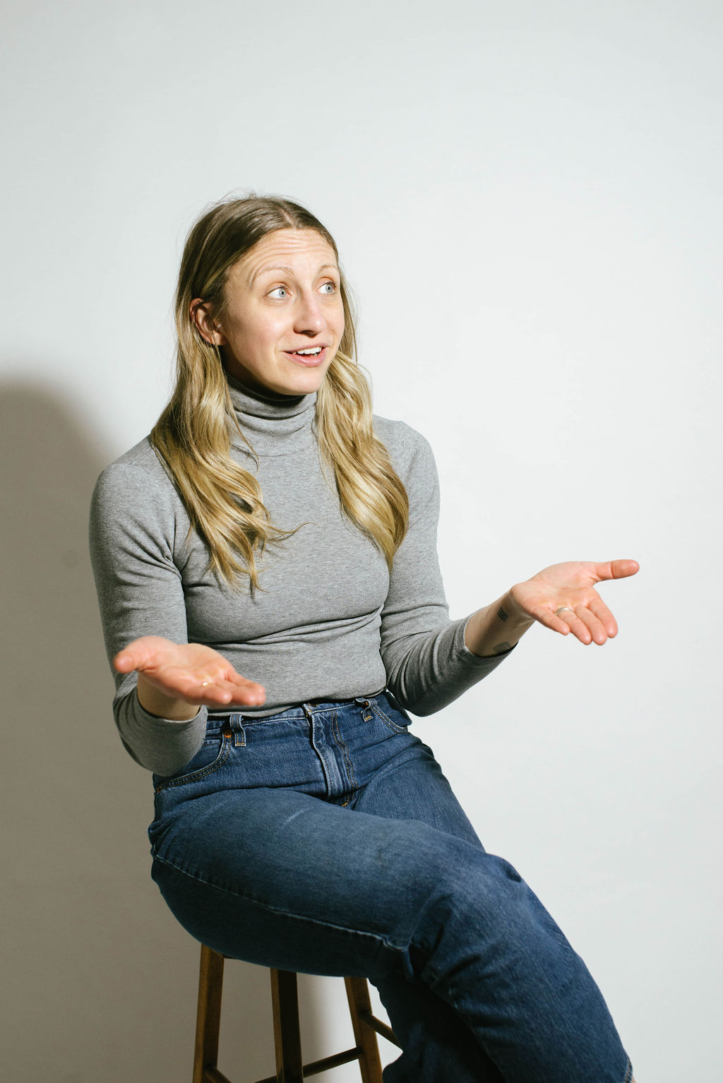 blonde woman wearing grey turtleneck and jeans sits on a stool looking up with her hands open palms up questioningly