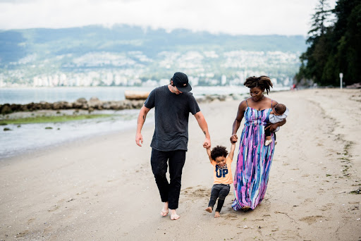 Mixed race family walks along the beach with their little boy between them and mom holding the baby