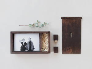 prints of a couple inside a wooden box sitting beside a wooden USB shows products that create passive income