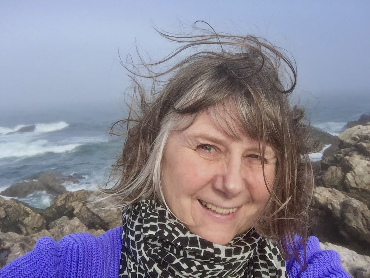 jill waterman, a photographer and writer for b&h photo takes a windy, smiling selfie on some rocks with a stormy ocean behind her.